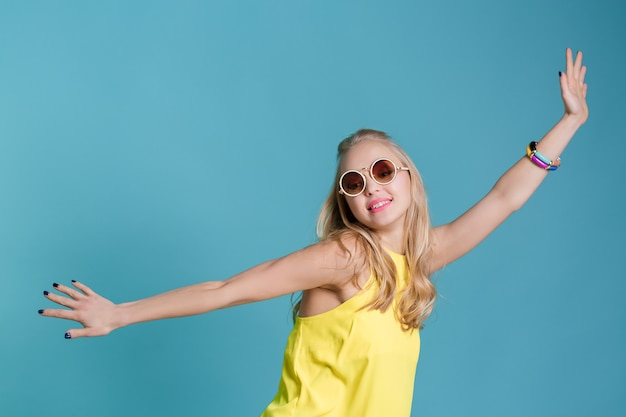 Portrait of beautiful blond woman in sunglasses and yellow shirt dancing on blue background carefree...