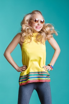 Portrait of beautiful blond woman in sunglasses and yellow shirt jumping on blue background carefree...