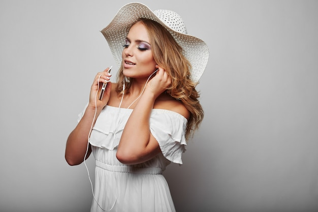Portrait of beautiful blond woman in white summer dress