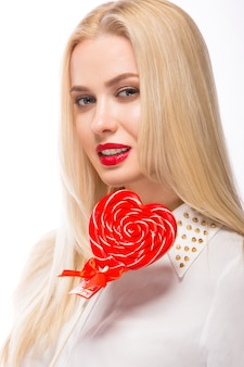 Portrait of beautiful blond woman with bright makeup and red candy heart in hand