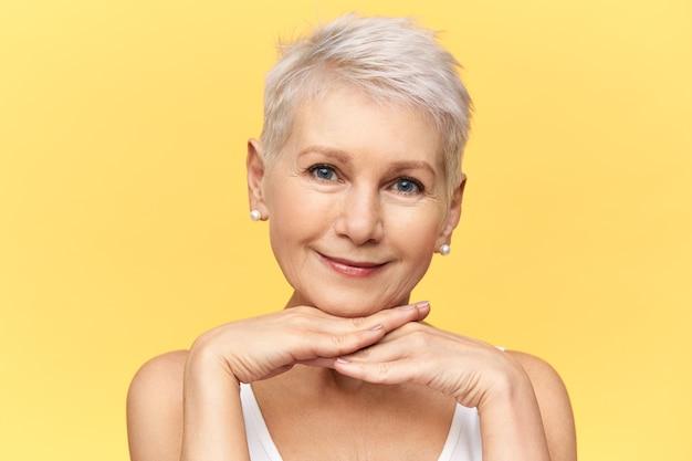 Ritratto di bella donna bionda europea pensionato con gli occhi azzurri e capelli corti in posa isolato con le mani sotto il mento, sorridente, ascoltandoti con attenzione.