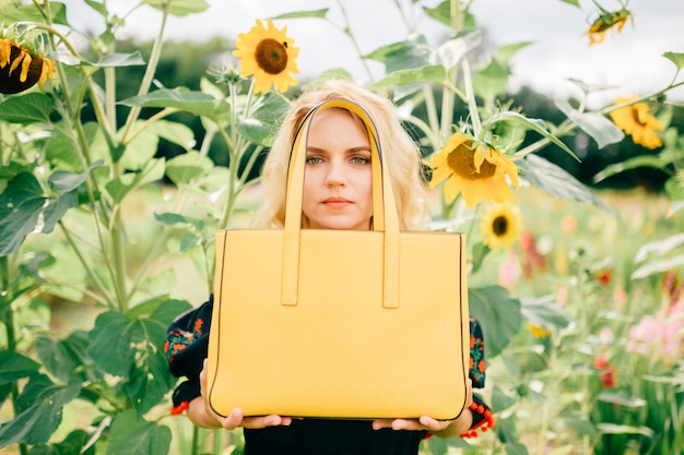 Portrait of beautiful blonde girl holding yellow bag in sunflower field