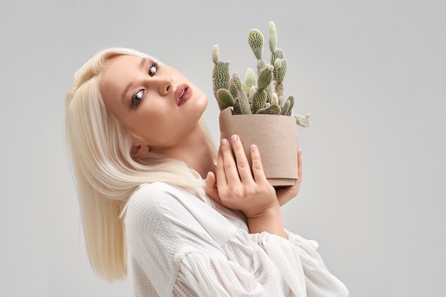 Portrait of beautiful blonde girl with make up and hairstyle wearing white blouse, looking at camera and holding pot with green cactus. pretty young woman buying plant for house