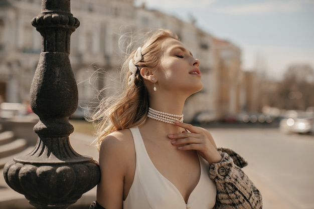 Portrait of beautiful blonde lady in stylish white silk dress, checkered jacket and pearl necklace gently touching neck and posing at city square
