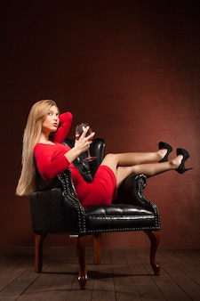 Portrait of beautiful blonde lying in big black leather arm-chair with wine glass.