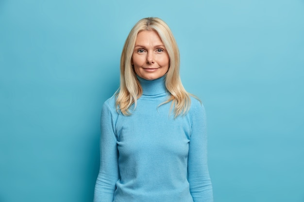 Portrait of beautiful blonde middled aged european woman looks directly at camera