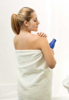 Portrait of beautiful blonde woman applying creme at bathroom