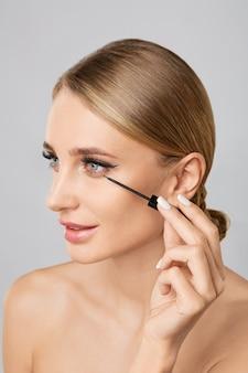 Portrait of beautiful blonde woman applying liquid eyeliner with brush. natural make up.