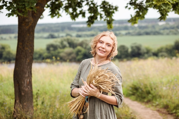 Portrait of beautiful blonde woman dressed in linen dress holding wheat bouquet. authentic lifestyle, vegan or ecology concept.