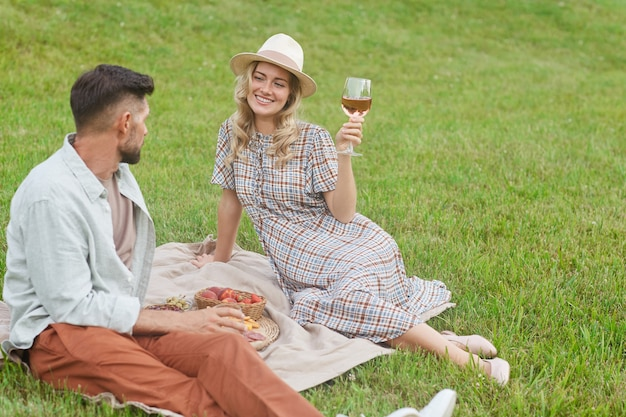 Portrait of beautiful blonde woman holding wineglass while enjoying picnic on green grass during romantic date outdoors