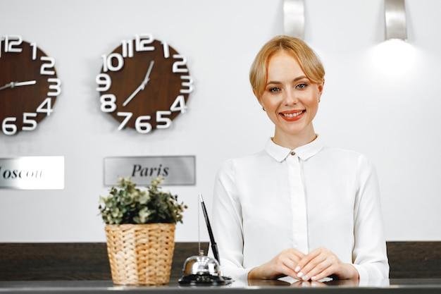 Portrait of beautiful blonde woman hotel receptionist close up