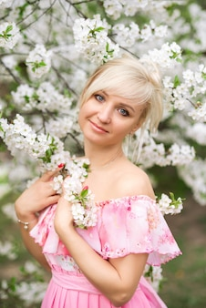Portrait of a beautiful blonde woman in a pink dress in a blooming garden in spring.