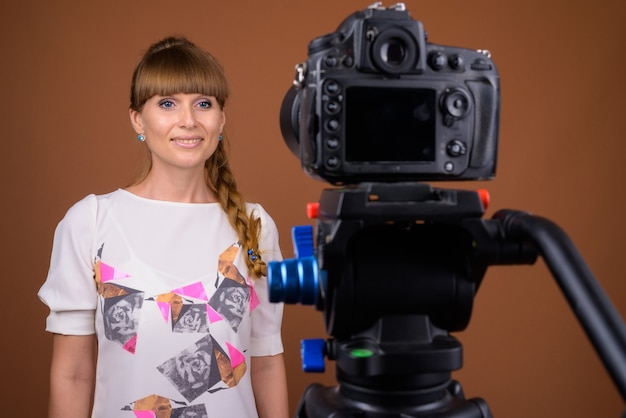 Portrait of beautiful blonde woman vlogging with camera