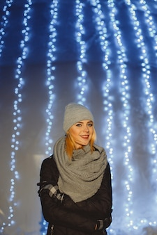 Portrait of beautiful blonde woman walking outdoors in a cold winter night