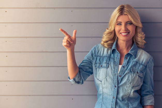 Portrait of beautiful blonde woman with blue eyes in jeans.