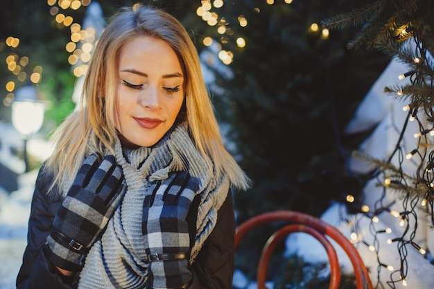Portrait of beautiful blonde young woman in black coat and scarf