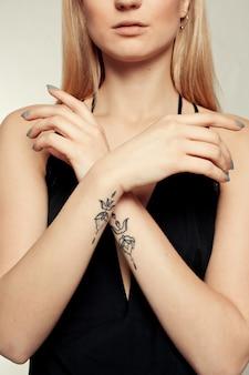 Portrait of beautiful blondewoman in black dress. fashion photo. closeup shot of hands
