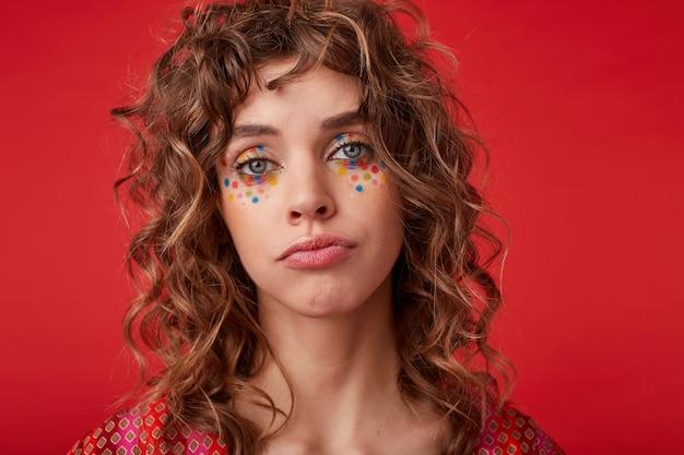Ritratto di bella giovane donna dagli occhi azzurri con acconciatura romantica e puntini multicolori sul viso cercando e increspando le labbra, isolato