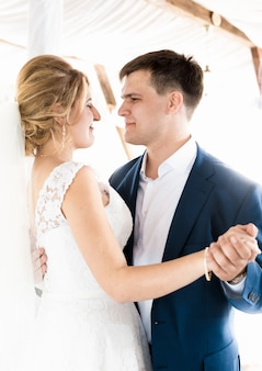 Portrait of beautiful bride and groom dancing at wedding ceremony
