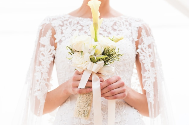 Portrait of the beautiful bride holding the bouquet