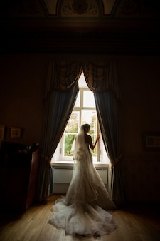 Portrait of beautiful bride at home. woman stand by the window in wedding dress