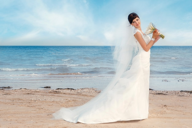 Portrait of beautiful bride is standing by the beach