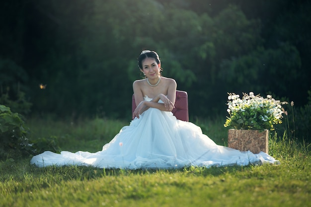 Portrait of beautiful bride sitting on the chair outdoors