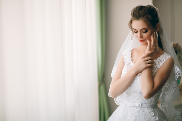 Portrait of beautiful bride in white silk dressing gown with curly hairstyle and long veil standing near window in bedroom, copy space