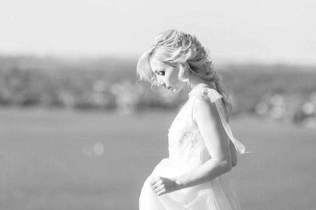 Portrait of the beautiful bride with bouquet of flowers in the nature. black and white photo