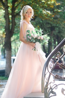 Portrait of the beautiful bride with bouquet of flowers in the nature. fine art photography.