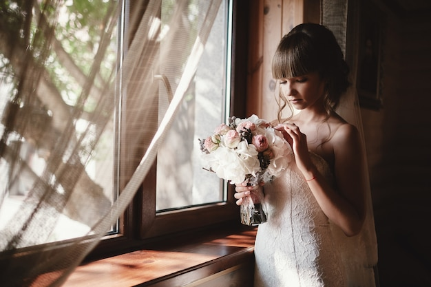 Portrait of a beautiful bride with a bouquet of roses and hydrangea indoor. pretty happy bride in luxury dress near the window. wedding morning preparation
