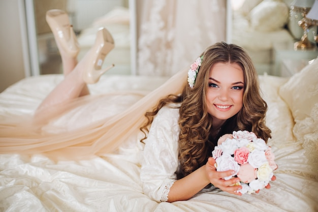 Portrait of beautiful bride with long hair in white lingerie looking at the camera, smiling.