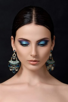 Portrait of beautiful brunet woman with blue earrings posing over black background