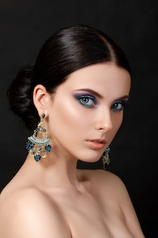 Portrait of beautiful brunet woman with blue earrings posing over black background.