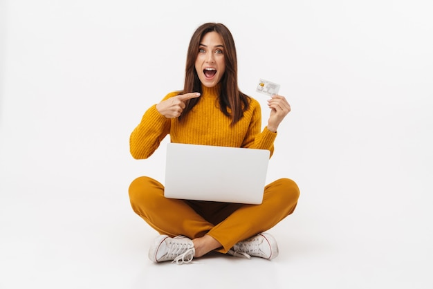 Portrait of beautiful brunette adult woman holding laptop computer and credit card while sitting with legs crossed isolated on white