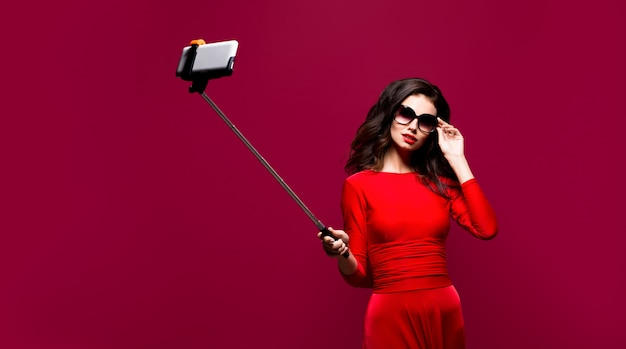 Portrait of beautiful brunette in awesome dress and red lips wearing sunglasses while making selfie with stick.