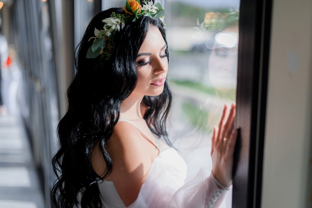 Portrait of beautiful brunette bride with closed eyes near the window on a beautiful sunny day