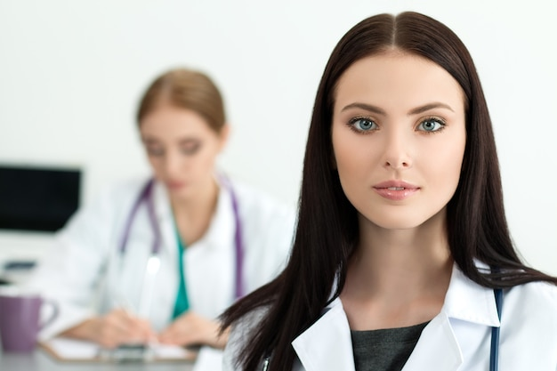 Portrait of beautiful brunette female medicine doctor with her colleague working. healthcare and medicine concept.