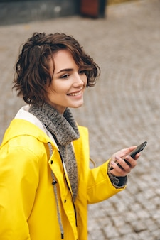 Portrait of beautiful brunette female walking on paving stones holding smartphone in hand scrolling feed in social network