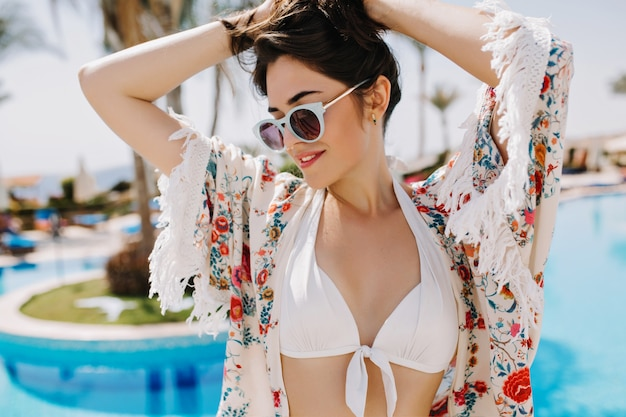 Ritratto di bella ragazza castana in bikini e camicia alla moda in posa con le mani in alto vicino alla piscina all'aperto. giovane donna elegante in occhiali da sole alla moda che riposa al resort e gode di vacanza.
