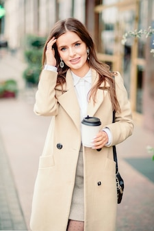 Portrait of beautiful brunette girl walking down the street
