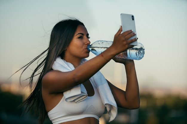 Portrait of a beautiful brunette girl with hair in running motion and athlete with fitness lifestyle is drinking water after running and is holding her smartphone making a video call