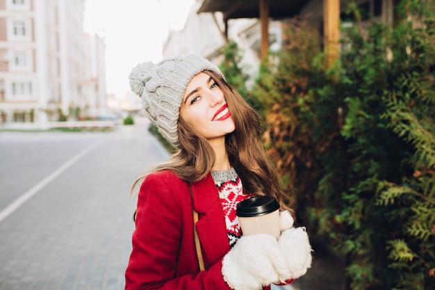 Bella ragazza castana del ritratto con capelli lunghi in cappotto rosso che cammina sulla strada in città. tiene il caffè da portare in guanti bianchi, sorridendo con le labbra rosse.