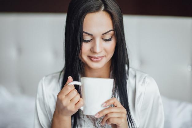 Ritratto di una bella ragazza bruna felice seduta nel suo letto la mattina e bevendo tè dalla tazza carina