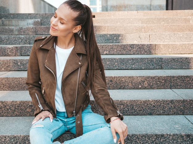 Portrait of beautiful brunette model dressed in summer hipster jacket and jeans clothes.