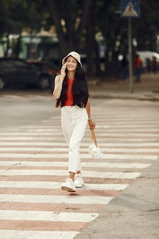 Portrait of beautiful brunette. model in summer city. woman walks with mobile phone.