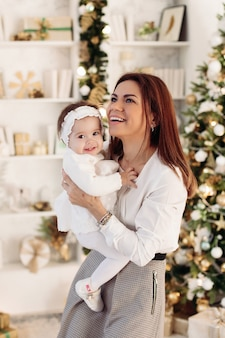 Portrait of beautiful brunette mother and happy little baby girl on her hands smiling and having fun together against decorated festive christmas tree at home