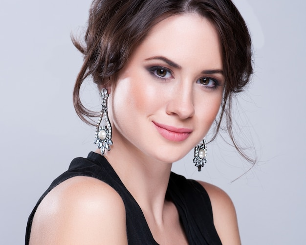 Portrait of beautiful brunette woman in black dress. cosmetic eyeshadows