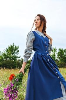 Portrait of a beautiful brunette woman in blue dress in the field