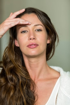 Portrait of beautiful brunette woman day dreaming in bathroom